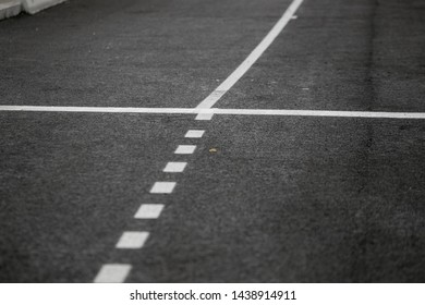 The texture of gray asphalt road. White markings on the track. Road trip. Big wide road.