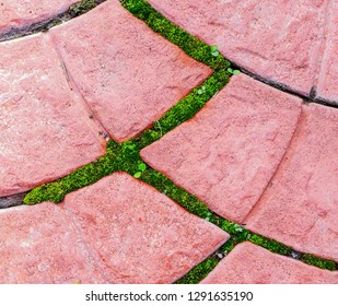 Texture of gray and pink patterned paving tiles on ground of street. Perspective view. Cement brick squared stone floor background. Concrete paving slab flagstone. Sidewalk pavement pattern.