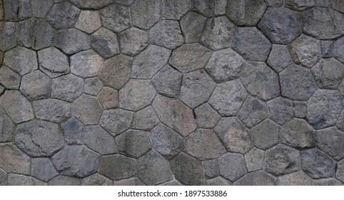 Texture of a gray stone wall. Smooth, cracked surface. Old castle wall of stone different shape. Part of a stone wall, for background or texture.