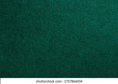 Texture of a green mat of poker cards.