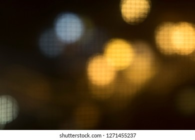 The texture of the grid and blurred lights in the distance