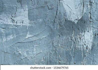 The texture of gypsum or alibaster cracked plaster on the wall is a thick layer. Gradient blue putty wall background