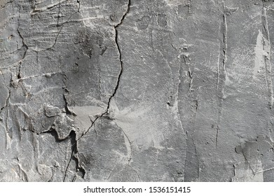 The texture of gypsum or alibaster cracked plaster on the wall is a thick layer. Gradient gray putty wall background