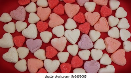 Texture of heart-shaped candies in white, red and violet color on red background