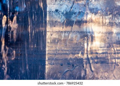 Texture of an ice block with a sunlight flare. Designer background. Close-up. The concept of global warming or permafrost.