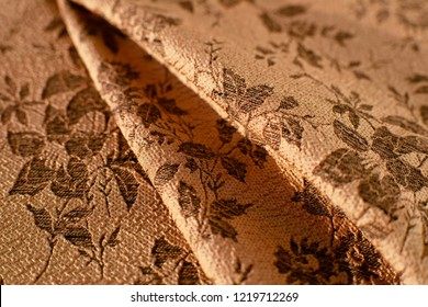 Texture of jacquard fabric. Brown pleated jacquard fabric creates a textural background. Fabric for sewing clothing and decorative items.