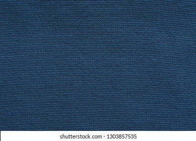 texture of knitted fabric or textile material of fashionable dark blue color for a uniform background or for wallpaper