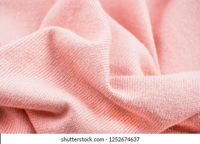 Texture of knitted sweater, closeup, on the background screen saver. Partially blurred background. Light pink color