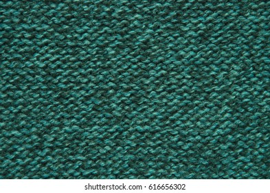 The texture of a knitted woolen fabric green.