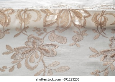 texture lace. a fine open fabric, typically one of cotton or silk, made by looping, twisting, or knitting thread in patterns and used especially for trimming garments.