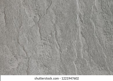 Texture of light gray stone with a rough and matte surface. Grunge background with space for text or image. Empty template and mockup for designers.