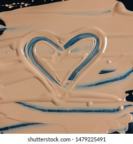 Texture of liquid foundation on dark surface with figure in the shape of heart. Cosmetics advertising concept