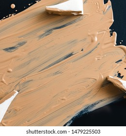 Texture of liquid foundation on dark surface with sponges for applying a tone. Cosmetics advertising concept