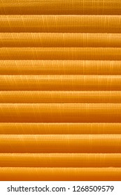 Texture of louver or jalousie, sunlight through the jalousie. Horizontal lines in orange.