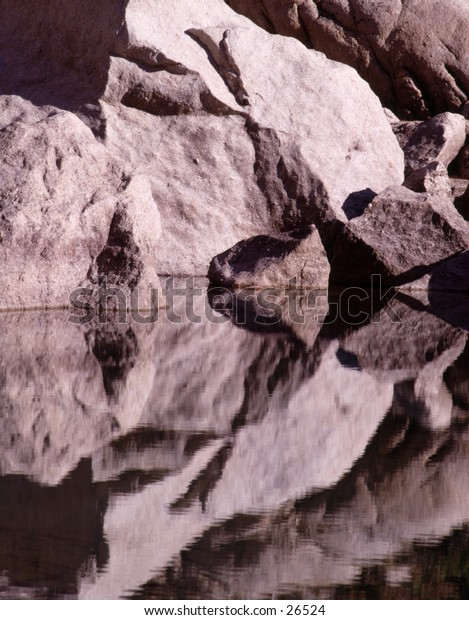 a texture made with reflection of rocks in a pond