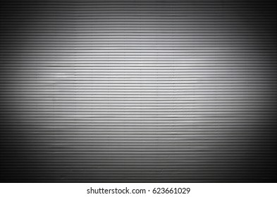 The texture of a metal wall or a surface of corrugated metal with invisible light sources that illuminate the middle of the platform for product placement
