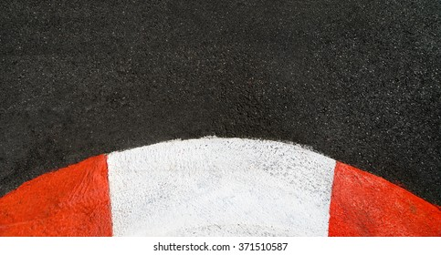 Texture of motor race asphalt and curved red white curb. Close up on Monaco Montecarlo Grand Prix street circuit