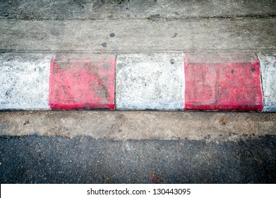 Texture of motor race asphalt and red white curb