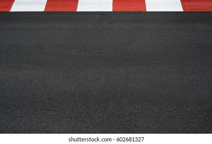 Texture of motor race asphalt and red white curb on Grand Prix street circuit