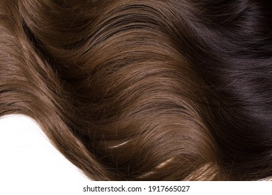 A texture of natural looking synthetic dark brown and walnut wavy curly hair, cold wave style, isolated on white