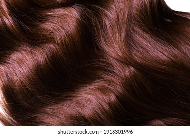 A texture of natural looking synthetic dark copper walnut wavy curly hair, cold wave style, on white background