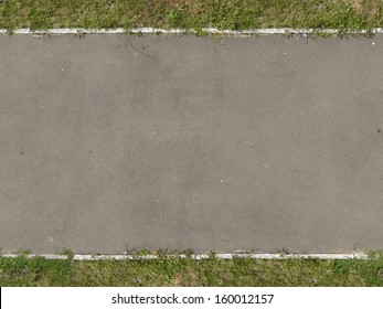 Texture of new, asphalt road in grey tone with grass at edges.