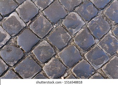 Texture of old black paving slabs. Pavement surface. Abstract diagonal background and texture for design.