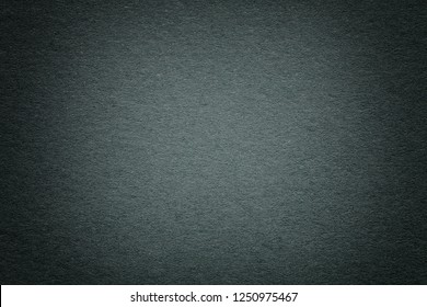 Texture of old dark green paper background, closeup. Structure of dense deep bluish kraft cardboard. Felt gradient pale olive backdrop closeup.