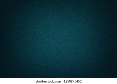 Texture of old dark navy blue paper background, closeup. Structure of dense deep bluish kraft cardboard. Felt gradient turquoise backdrop closeup.