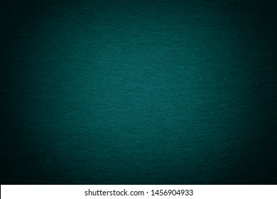 Texture of old dark navy blue paper background, closeup. Structure of dense emerald kraft cardboard. Felt gradient turquoise backdrop closeup.