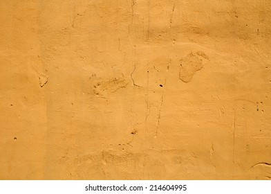 Texture of old dirty wall with scratched plaster yellow