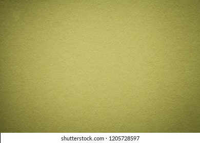 Texture of old olive paper background, closeup. Structure of dense light green kraft cardboard. Felt gradient backdrop closeup.