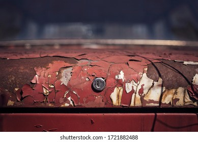 The texture of the old red trunk of a car with cracked multi-layer paint.