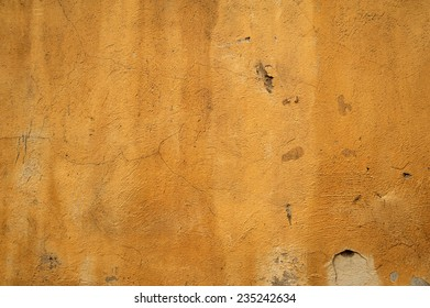 Texture of old rustic wall covered with yellow stucco
