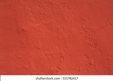 Texture of old rustic wall covered with red stucco