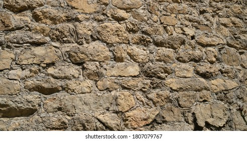 Texture of old stones of various forms with seams. Close up of shabby masonry. Stone wall from uneven different ancient friable cobblestones.