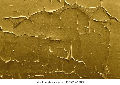 Texture of the old weathered rough peeling airbrushed golden color paint on concrete wall. Background for design.