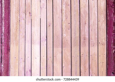 Texture of old wooden fence painted in pink color