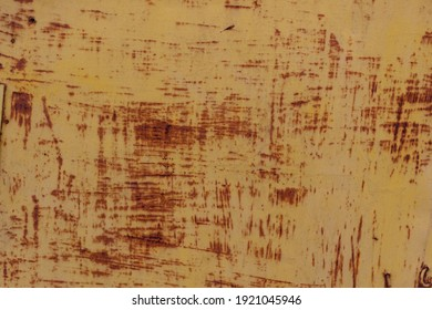 Texture of an old yellow fence with rust. Background.