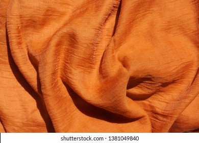 Texture of orange fabric. Texture t is light brown textile material. Auburn scarf closeup. Dark Yellow Palatine.