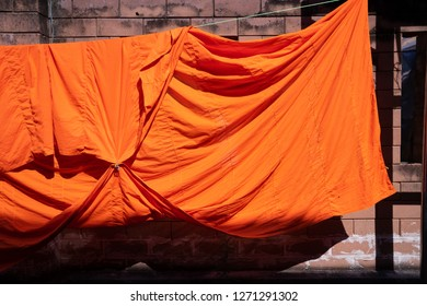 texture of orange robe of a buddhist monk or novice hanged on wire