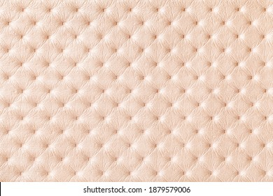 Texture of pearl beige leather background with capitone pattern, macro. Cream textile of retro Chesterfield style. Vintage fabric backdrop.