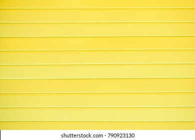 The texture of a plastic wall with horizontal stripes of yellow boards, background