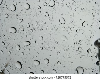 Texture from rain drop on car glass, sky and rain clouds are background.