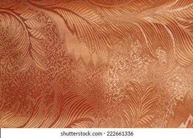 Texture of red and beige satin patterned curtains with folds