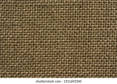 texture of rough fabric or textile material with a perepoleteniye closeup for a fashionable background or for wallpaper of brown straw color