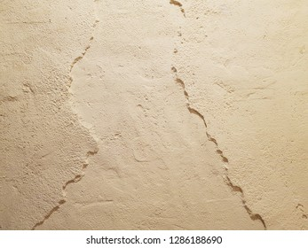 The texture of a rough uneven wall with flaws. Old cement wall for background with copy space.