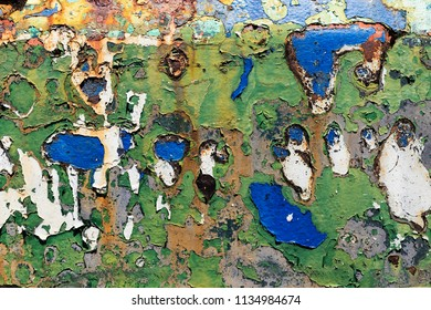 Texture of rusty colorful metal background with a peeling cracked layers of paint.