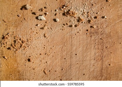 Texture of the scratched wooden board with bread crumbs. Bright sunlight early in the morning. Macro background with space for text.