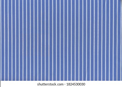 The texture of a simple blue cotton fabric with white cross stripes. The background of natural soft tissue is blue.